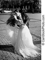 Monochrome shot of kissing bride and groom on street at windy da