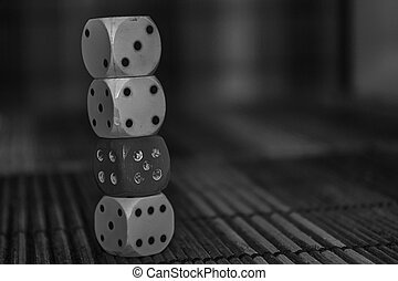 Monochrome Stack of three plastic dices and one red dice on wooden board background. Six sides cube with black dots. N 3, 4, 5, 6.