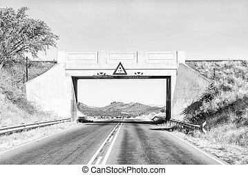 Monochrome view of railway bridge frames mountain scene near Windhoek