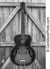 Vintage acoustic guitar hanging on an old, crooked, weatherbeaten fence, monochrome.