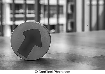 Monochrome Wooden toy arrow on the circle on the table.
