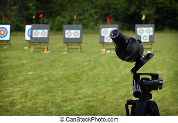 Monocular fixed on tripod on archery range during ...