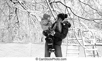 Monohrome portrait of mother with her cute son in jacket and hat playing with snow covered tree on the playground in the Park