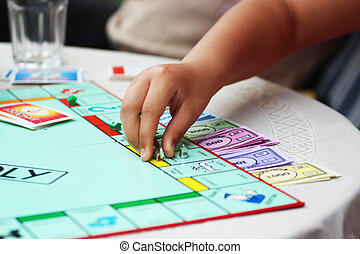 Monopoly game - Child white hand playing a game - activity...