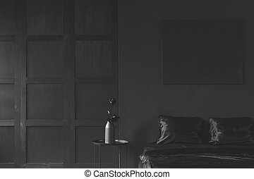Monotone dark black bedroom interior - Rose on table next to...
