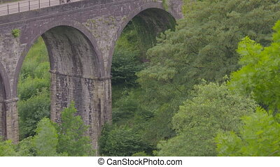 Medium low angle still shot of arched Monsal Headstone Viaduct Bridge with thick lush green valley vegetation, and cyclists riding at the top, Monsal Trail, Peak District, UK