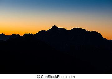 montaña, silhoette, de, alpes austríacos, en, salida del sol, encendido, cielo
