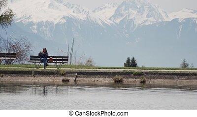 montagne, femme, lac, images, banc, jeune, prend, surprenant, assied, vue, smartphone, sur, bois