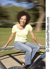 montando, mulher, parque, jovem, rotunda