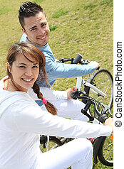 montando, par, bicicletas, jovem