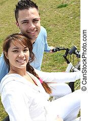 montando, par, bicicletas, parque, jovem