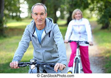 montando, sênior, bicicletas, par
