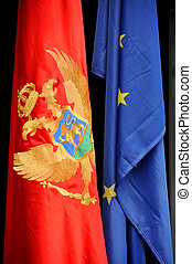 Montenegrin and European flag in front of modern political...