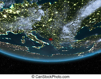 Montenegro at night highlighted in red on planet Earth with...