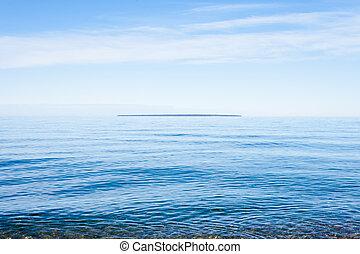 Montreal Island far out on horizon on calm Lake Superior, Ontario, Canada