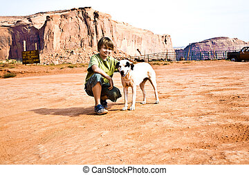 Monument Valley, boy strokes a beautiful lovely dog in the...