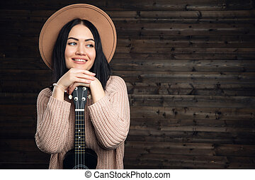 mood., ragazza, canto, divertente, ukulele, positivo, giovane, fondo., hipster, il portare, vendemmia, ballando., scuro, divertimento, cappello, parete, legno, detenere, gioia, chitarra, piccolo, gioco