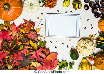 Moody, autumn background with colorful leaves and blank tablet with copy space