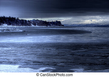 Moody blue landscape of Mud bay near Homer, Alaska with dark storm clouds.