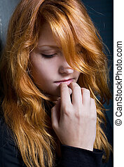 Moody dark portrait of a young redhead girl.