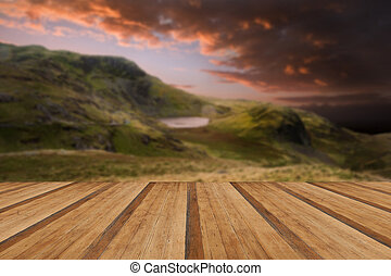 Moody dramatic mountain sunset landscape with wooden planks floo