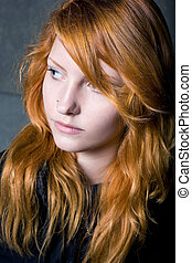 Moody portrait of a beautiful young redhead girl.