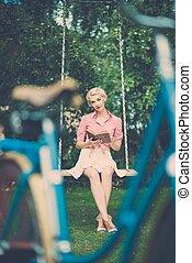 mooi, blonde , retro, vrouw zitten, op, een, luchtschommel, met, een, boek