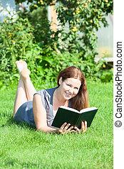 mooi, glimlachende vrouw, het liggen, op, wei, met, boek, in, hand, en, kijken naar van fototoestel