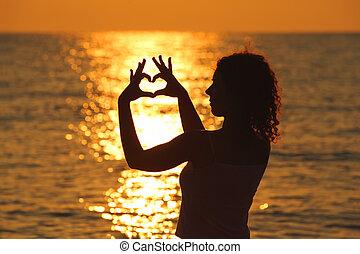 mooi, hart, vrouw, haar, jonge, zee, handen, maakt, ondergaande zon