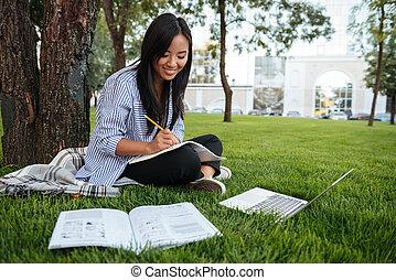 mooi, het behouden, buiten, zittende , studerend , draagbare computer, gras, verslag, terwijl, notitieboekje papier, student, online, aziaat
