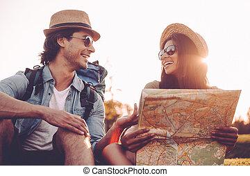 mooi, het onderzoeken, aanzicht, eigen, hoek, kaart, paar, zittende , jonge, samen, hun, terwijl, groene, laag, buitenshuis, bevinding, het glimlachen, gras, rugzakken, way.
