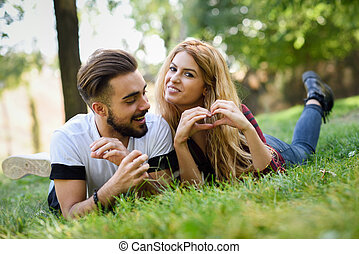 mooi, jong paar, het leggen, op, gras, in, een, stedelijke , park.
