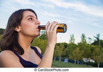 mooi, jonge, brunette, het drinken van een fles, van, bier, in, de, park.