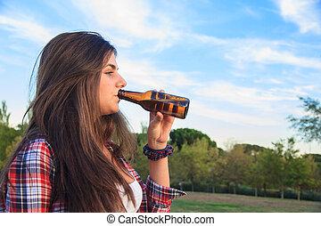 mooi, jonge, brunette, met, blauwe ogen, het drinken van een fles, van, bier, in, de, park.
