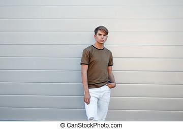 mooi, jonge man, in, een, classieke, mode, t-shirt, en, wit gehijg, dichtbij, een, moderne, muur