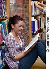 mooi, jonge vrouw , het lezen van een boek, zitting op de verdieping