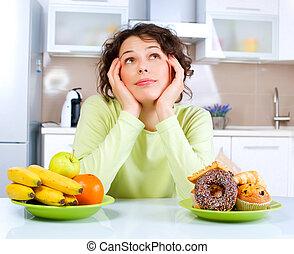 mooi, jonge vrouw , kies, tussen, vruchten, en, zoetigheden