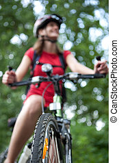 mooi, jonge, vrouwlijk, fietser, outddors, op, haar, de fiets van de berg, (shallow, dof;, selectief, focus)