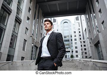 mooi, jonge, zakenman, in, kostuum, staand, dichtbij, commercieel centrum