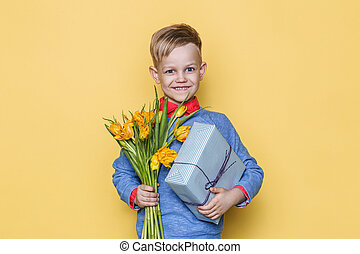 mooi, jongen, vasthoudende bloem, bos, en, cadeau, box., valentine, day., birthday., moeder, day., studioportret, op, gele achtergrond