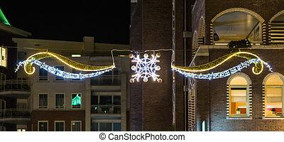 mooi, kerstversiering, met, lichten, hangend, tussen, enig, gebouwen, in de stad, straten, op de avond, tijd