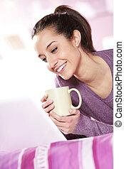 mooi meisje, glimlachen, op, de, draagbare computer, met, een, kop van koffie, in, hand