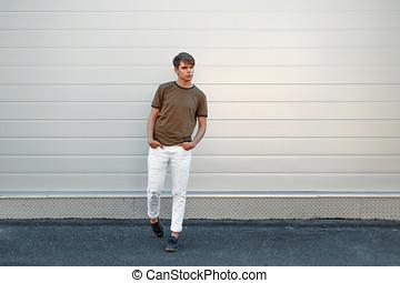 mooi, modieus, jonge man, in, een, mode, t-shirt, en, wit gehijg, met, zwart leder, broek, dichtbij, de, grijs, metaal muur