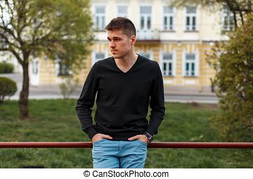 mooi, modieus, man, in, een, zwarte t-shirt, en blauw, broek, buitenshuis
