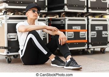 mooi, modieus, man, met, sunglasses., en, een, pet, in, een, mode, witte t-shirt, en, zwart gehijg, zit, dichtbij, de, containers, op de straat