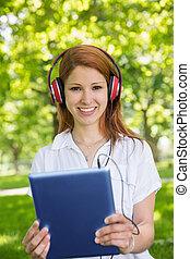 mooi, roodharige, gebruik, haar, tablet pc, terwijl, horende muziek, in, t