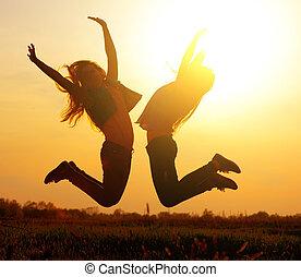 mooi, silhouette, op, meiden, springt, ondergaande zon
