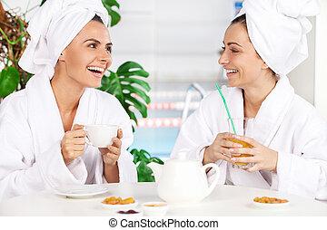 mooi, spa., zittende , uitgeven, thee, elke, badjas, jonge, klesten, terwijl, anderen, twee, tijd, voorkant, drinkt, zwembad, vrouwen