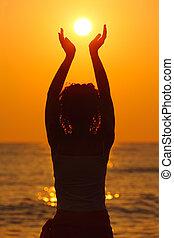 mooi, staand, vrouw, strand, zon, schouwend, jonge, holdingshanden, ondergaande zon