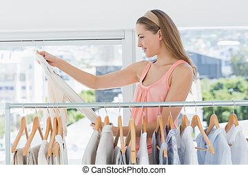 mooi, vrouwlijk, manierontwerper, kijken naar, hemd, naast, rek, van, kleren, in, de, winkel